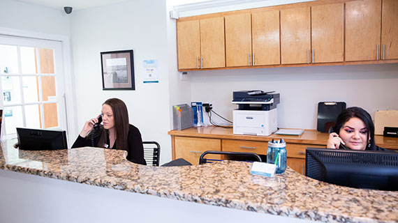 Front Desk staff answering patient calls at Elite Dental of Natick