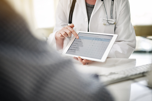 Shot of a doctor showing patient online forms on a digital tablet in her office