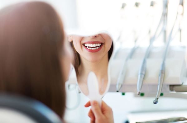Woman looking at her smile in a mirror at Elite Dental of Natick in Natick, MA